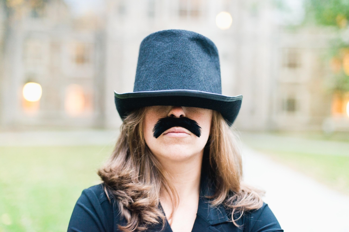 Daisy wearing a funny mustache and hat for an engagement photo