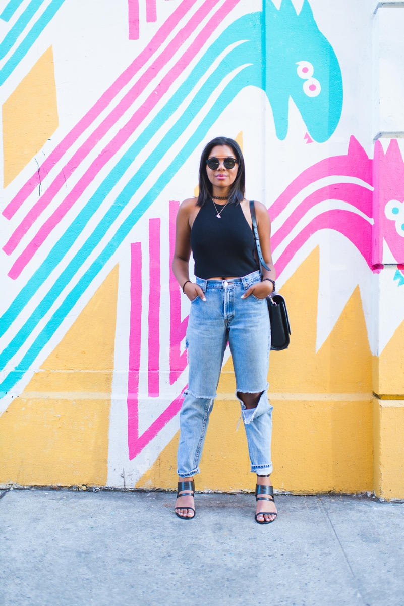 Devine Blacksher wearing boyfriend jeans in front of a mural