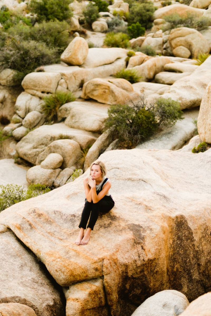Photographer Lindsey Boluyt sits admit the rock formations in Joshua Tree National Park