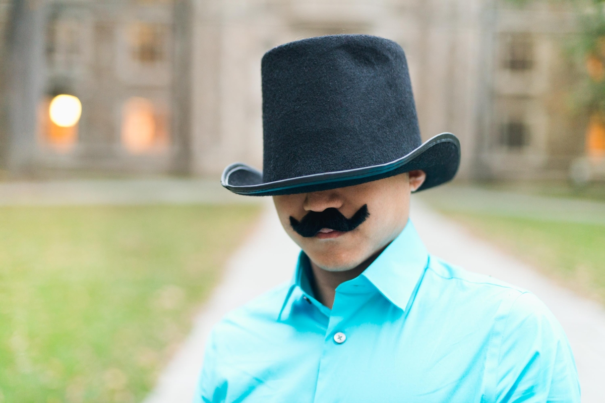 Vincent wearing a funny mustache and hat for an engagement photo