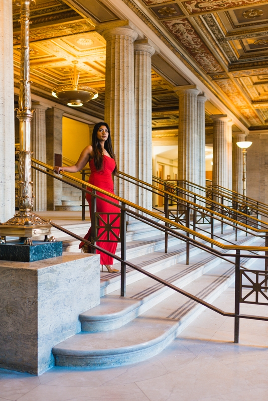 An elegant red dress in an all-marble foyer